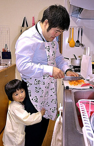 帰宅後すぐに夕飯を作る荒木隆幸さん。長女の咲ちゃんが抱きついてきた=新潟県長岡市