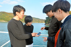 船の上でアプリを開いて位置を確認する山本竜也さん(左から2番目)ら=鳥羽市池上町