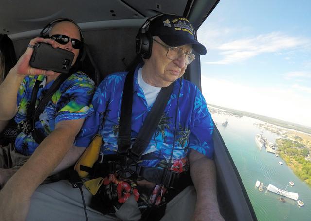 米ハワイ州ホノルルの真珠湾で5日、海底に沈んだ戦艦アリゾナの上に建てられた記念館をヘリコプターの窓から見下ろす男性。男性は1941年の日本軍による真珠湾攻撃の際に同艦に乗っていた=ロイター