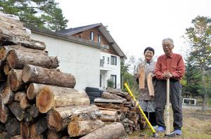 自宅の庭でまき割りをする松沢宗洋さん(右)と妻の寿子さん=長野県小谷村