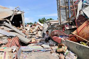 7日、強い地震が襲ったインドネシア・アチェ州で、がれきの上にしゃがみ込む少年=AP