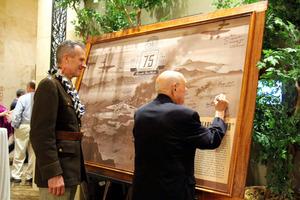 真珠湾攻撃から75年を迎える記念行事で、額縁にサインをする退役軍人=6日、ホノルル、平山亜理撮影