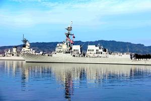 真珠湾で7日、攻撃で沈没した戦艦アリゾナに対し、軍艦から追悼する米兵ら=ホノルル、平山亜理撮影