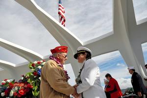 米ハワイ・ホノルルの真珠湾で7日に開かれた追悼式典で従軍牧師と握手する元軍人(左)=ロイター