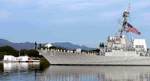 真珠湾で7日、沈没した戦艦アリゾナの上に立つ記念館(左奥)の前を通って追悼する軍艦
