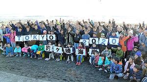 歓声を上げて、東京五輪サーフィン会場決定を喜ぶ地元サーファーら=千葉県一宮町