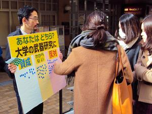 教職員有志(左)の持つボードに、シール投票する学生たち=岐阜大学、椎名貴彦さん提供