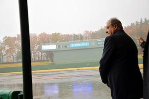 雨の中、県営あづま球場を視察する世界野球ソフトボール連盟のフラッカリ会長=11月19日、福島市