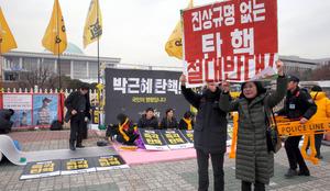韓国の朴槿恵(パク・クネ)大統領に対する弾劾(だんがい)訴追案の採決を控えた国会前で8日、可決を目指して座り込みを続ける野党と、反対を訴えるプラカードを掲げる保守団体のメンバー=ソウル、東亜日報提供