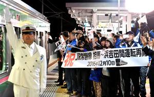 新設された山下駅を出発する仙台行きの下り始発列車を、横断幕を持った地元住民が見送った=10日午前5時42分、山元町、福留庸友撮影