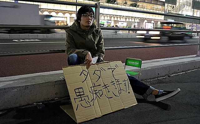 新宿駅南口近くの路上で。「客」用の折りたたみイスも用意する