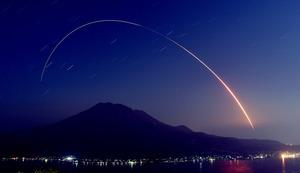 桜島上空に弧を描くロケットの光跡(約7分間露光)=鹿児島市吉野町、全日写連二宮忠信さん撮影