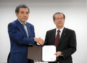 包括連携に調印し、握手をする広島平和文化センターの小溝泰義理事長(右)と広島大の越智光夫学長=広島市中区