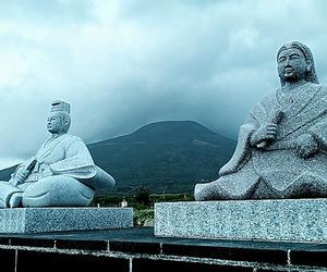 宇喜多秀家(左)と豪姫の像。岡山城がある西方を見つめている。豪姫は同行を許されなかったが、いまは2人並ぶ。後方は八丈富士。雨雲が垂れ込めてきた=東京・八丈島