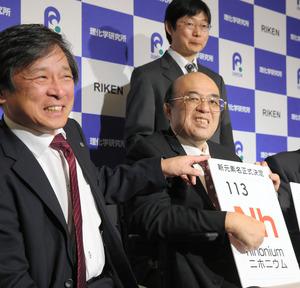 新元素記号正式決定後の会見で、パネルを手に笑顔を見せる理化学研究所チーム=1日、福岡市