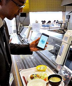 山陰合同銀行の本店内の社員食堂での仮想通貨を使った実験。スマホをタブレットにかざして決済する=11月、松江市魚町