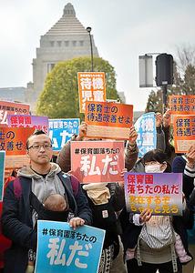 「保育園落ちたの私だ」と書かれた紙を掲げて国会議事堂前に立つ人たち=今年3月、東京都千代田区