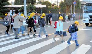 県道の事故現場近くを歩いて登校する児童ら。保護者が黄色い旗を持って誘導する=上尾市上野