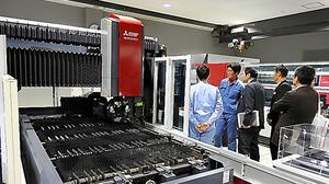三菱電機の商談会。金属板にレーザーで穴を開けて加工する装置は、中国のスマートフォン向けの設備投資で好調だという=9日、兵庫県尼崎市