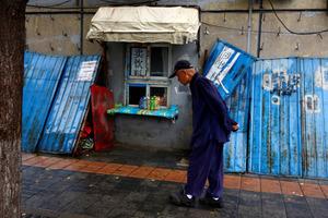 北京で飲料などを売る店の前を歩く高齢の男性=ロイター