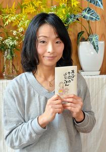 絵本「あんぽと今夜のばんごはん」を手にする小山香代さん=大分県臼杵市