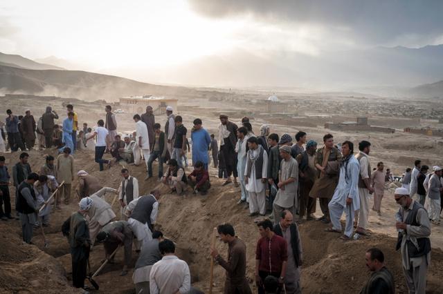 2016年7月、ISに関連するとみられる2件の自爆テロによる犠牲者を埋葬する人たち=Adam Ferguson/(C)2016 The New York Times。アフガンでは超過激派集団が勢いづいているという