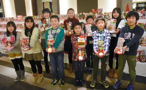 手作りのクリスマスブーツを手に集まった草津市と福島県伊達市の子どもたち=17日夜、草津市