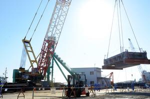 鉄骨がクレーンにつり上げられ、海側から運ばれた=東京電力福島第一原発、代表撮影