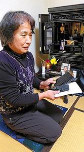 仏壇の前で夫の遺品を手にする西村トシ子さん=東京都足立区