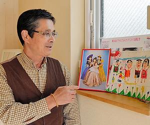 孫の書いた家族の絵を見る大渡和公さん