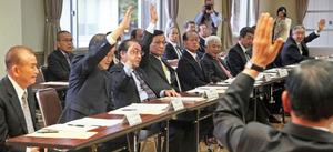 マイカー規制の延長に賛成の挙手をする出席者。富士観光開発は賛成、富士急行は反対と、観光業者の意見も割れた。右端手前は堀内茂会長=富士河口湖町船津