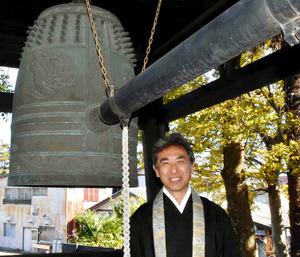 15代目住職の今井一光さんと梵鐘=静岡県牧之原市、北川サイラ撮影