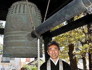 15代目住職の今井一光さんと梵鐘=静岡県牧之原市