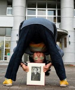 父の写真を手に股のぞきをする斎藤永子さん=仙台市青葉区の東北大学川内南キャンパス