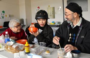 昼食を勢いよく食べる尾野一矢さん(中央)を笑顔で見つめる剛志さん(右)とチキ子さん=12月7日、厚木市七沢の障害者施設