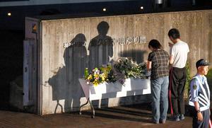障害者を狙った殺傷事件が起きた相模原市緑区の障害者施設「津久井やまゆり園」前で花を手向け、祈る人たち=7月27日