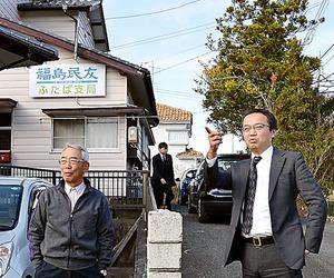 ふたば支局の前で根本賢仁さんと話す白坂俊和記者(右)