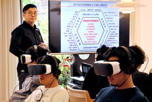 VRで認知症を体験する学生たち。下河原忠道社長(左)がモニターを使って補足説明をした=10月27日、千葉県船橋市