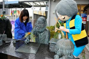 水木さんのブロンズ像にしめ縄を飾る清掃参加者(左)と鬼太郎の着ぐるみ=境港市大正町