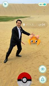鳥取砂丘でポケモンと一緒にポーズを取る平井伸治知事(県提供)
