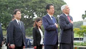雨の中、国立太平洋記念墓地で胸に手をあてる安倍晋三首相(中央)=26日午前、米ハワイ・ホノルル市、代表撮影
