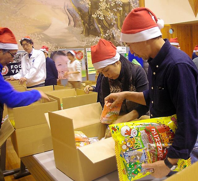 フードバンク山梨「こども支援プロジェクト」で、食料やプレゼントの箱詰め作業をするボランティアら=23日、山梨県南アルプス市