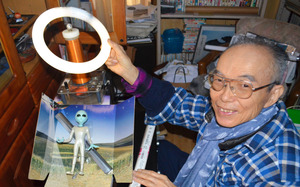 「テスラコイル」を使って光らせた蛍光灯で、宇宙人の人形を照らす木下次男さん=福島市飯野町