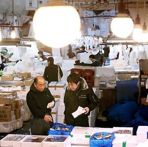 築地市場に買い付けに来た客と話をする仲卸店「亀谷」の亀谷直秀社長(左)=21日午前、東京都中央区、西畑志朗撮影