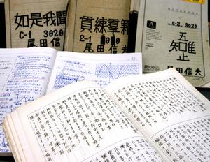 尾田信夫死刑囚が獄中で作成したノートの数々。日記や俳句、数学の試験問題の解法などが記されている=福岡市中央区、河合真人撮影