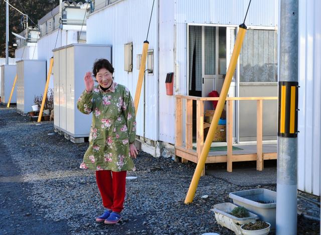 「また来てね」。引っ越した仮設住宅の前で手を振る佐々木テルさん=岩手県大槌町大槌