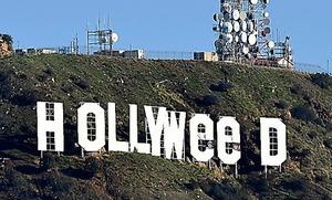 1日、米ロサンゼルスの丘にある有名な看板「HOLLYWOOD」が「HOLLYWeeD」と変えられた=AFP時事