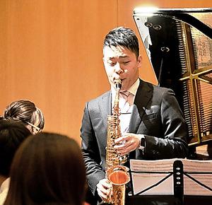 サックスを演奏する板倉健太さん=福島県いわき市