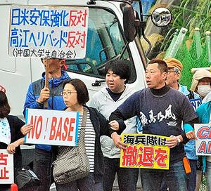 参加者は腕を組んで歌を歌い、抗議した=5日午前7時15分、沖縄県名護市