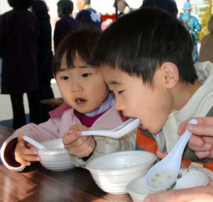 七草がゆを食べる子どもたち=平塚市札場町の長楽寺